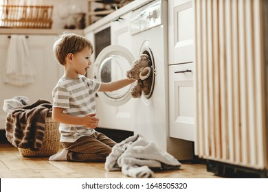 happy little funny householder child boy in laundry   with washing machine