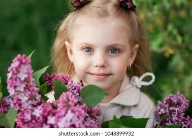 happy little girl 5 years old with a bouquet of lilacs in the spring on the street