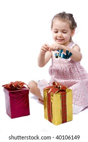 Happy little girl about to open her Christmas presents, playing with a blue ribbon. White background