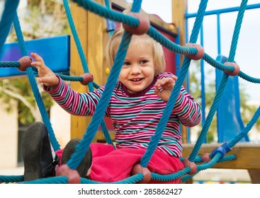 Happy little girl at action-oriented playground in summer