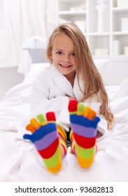 Happy little girl after bath wearing bathrobe and colorful sock