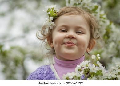 Happy little girl among white flowers