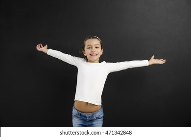 Happy little girl with arms open in front of a blackboard