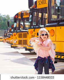 Happy little girl with backpack next to school bus. Back to school concept.