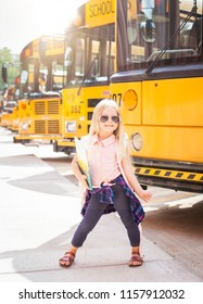 Happy little girl with backpack walking next to school bus. Back to school concept.
