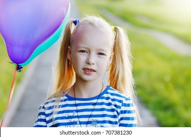 Happy little girl with balloons on nature.