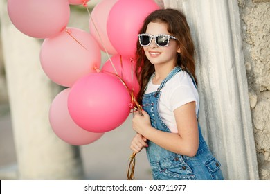 Happy little girl with balloons summer portrait. Hipster look child girl 10 year old with sunglasses and balloons wear jeans dress and posing outdoors at sunset. Cute kid friendly smiling outdoors.