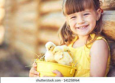 Happy little girl with a basket of small chickens sitting outdoor