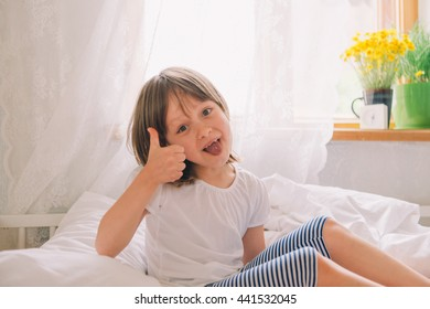 happy little girl in the bedroom. beautiful girl in bed. pretty little girl sitting in bed and smiling. flowers on the window. Light room. girl awoke. time to wake up
