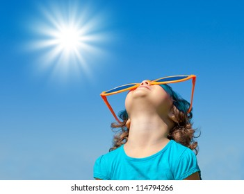 Happy little girl with big sunglasses looking at the sky with sun in summer