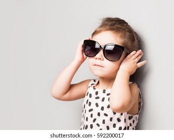 Happy little girl with big sunglasses. Fashionable