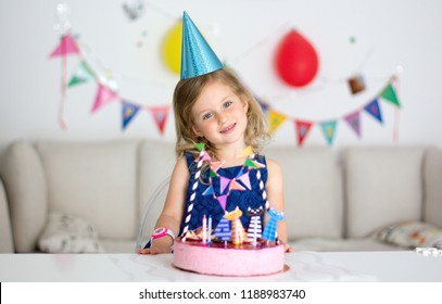 Happy little girl with birthday cake. Celebrate Happy Birthday Party with colorful decor.