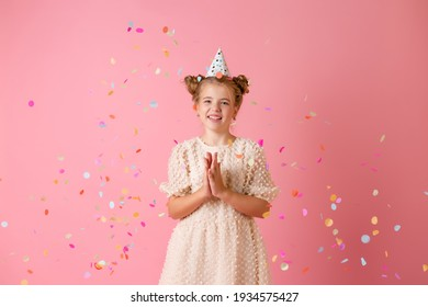 Happy little girl in a birthday cap blows off her palms multicolored confetti on a pink background in the studio