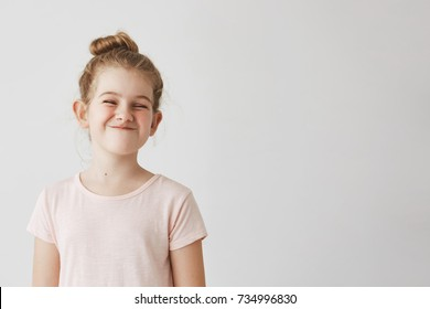 Happy little girl with blond long hair in bun hairstyle funny smiling with losed eyes, making silly faces on school photoshoot.