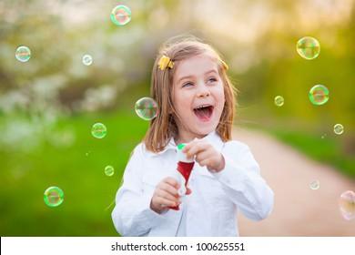 Happy little girl blowing soap bubbles
