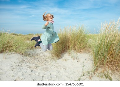 Happy little girl in blue dress jumping on beach of Baltic sea at sunny day