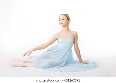 Happy little girl in a blue dress is sitting on the floor on a white background