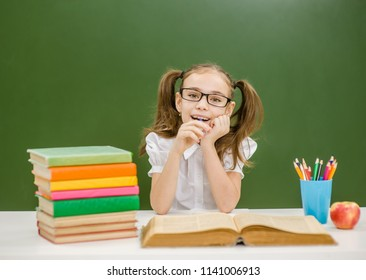 Happy little girl with books on the background of a school board looking at camera