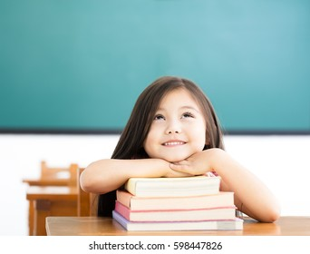 happy little girl with books and thinking in classroom