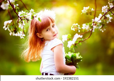 Happy little girl with a bouquet of lilies of the valley having fun in the blooming spring garden
