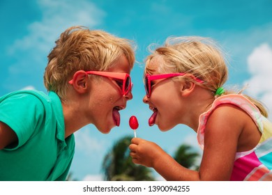 happy little girl and boy with lollipop on summer vacation