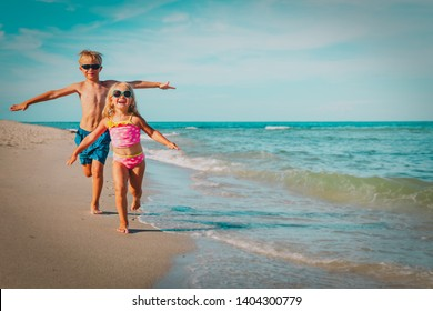 happy little girl and boy run fly play with waves on beach