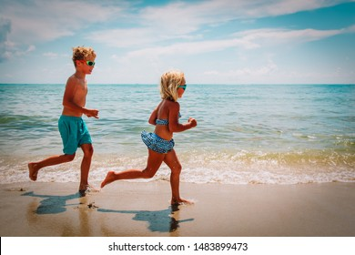 happy little girl and boy running at beach