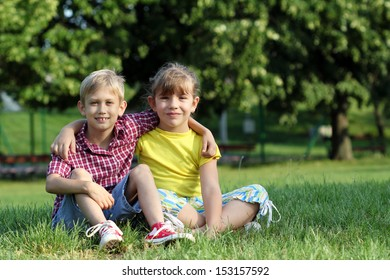 happy little girl and boy sitting on grass in park