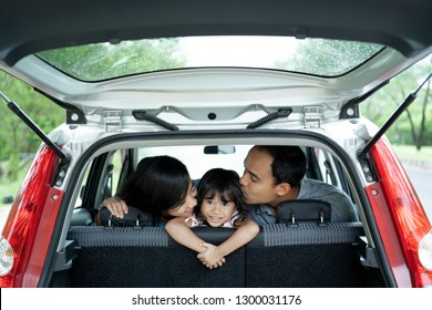 happy little girl in a car because mother and father loving her with kissing when vacation