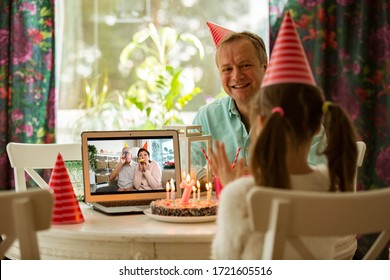 Happy little girl celebrating birthday at home with parents and grand parents on video call. Laptop with senior couple online, cake with candles on table.