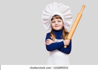 Happy little girl in chef uniform holds rolling pin isolated on light background. Kid chef. Cooking Process Concept