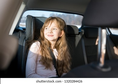 Happy little girl in child car seat