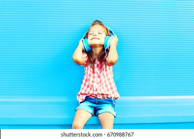 Happy little girl child listens to music in headphones on a colorful blue background