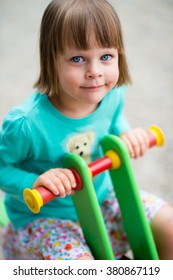 Happy little girl child on children playground - very shallow depth of field - summer, childhood, leisure and people concept