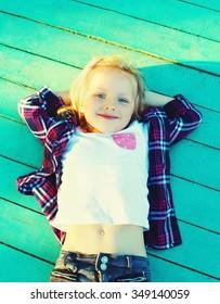 Happy little girl child resting on a wooden floor, hands behind head