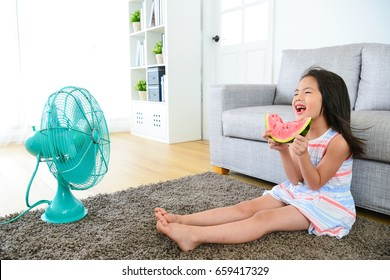 happy little girl children sitting on living room floor blowing electric fan cool wind and eating fresh watermelon feeling comfortable at summer.