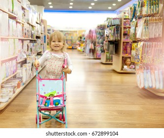 Happy little girl chooses toys in a children's store. Child in toy section of supermarket. Educational toys for kids