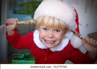 Happy little girl with the Christmas hat making funny faces