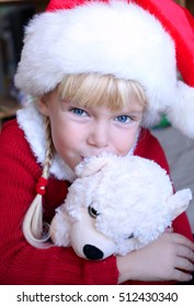 Happy little girl with the Christmas hat and Christmas gift hugging her favorite Teddy Bear