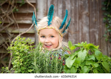 Happy little girl in colorful Indian headband standing in the garden surrounding by fresh green herbs