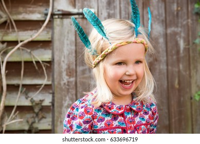 Happy little girl in colorful Indian headband standing in the garden