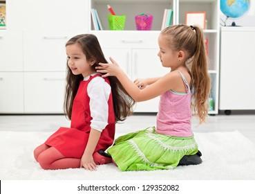 Happy little girl combing her girlfriend's hair