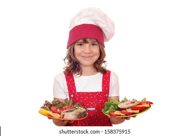 happy little girl cook holding plate with salmon seafood