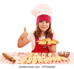 happy little girl cook with rolls and thumb up