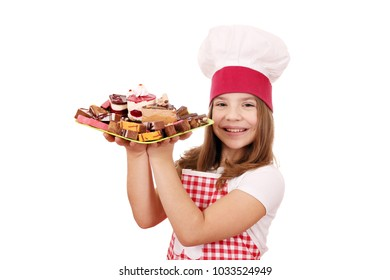 happy little girl cook with sweet cakes dessert on plate