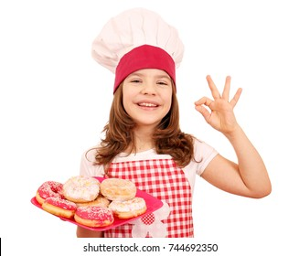 happy little girl cook with sweet donuts and ok hand sign