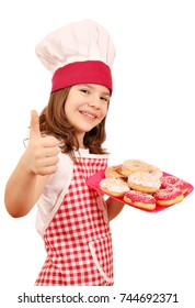 happy little girl cook with sweet donuts and thumb up