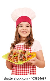 happy little girl cook with tacos on plate