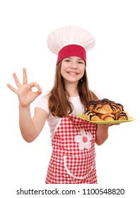 happy little girl cook with tasty croissant and ok hand sign