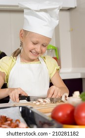 Happy little girl in a cooks uniform and white toque smiling as she chops mushrooms on a wooden chopping board in the kitchen
